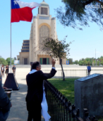 El Padre Raúl Arcila asperja agua bendita sobre la placa de bronce recordatoria.